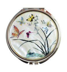 Une belle image de papillons et d'un plant d'orchidée décore le couvercle du miroir