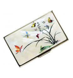 C'est un élégant porte-cartes de visite avec une illustration nacrée de papillons et de fleurs d'orchidé