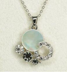 Le pendentif est réalisé en nacre blanche et décoré avec des cristaux de taille différente