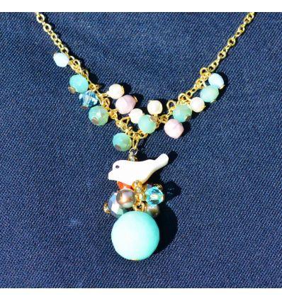 Le pendentif du collier est réalisé en jade de couleur bleu et un oiseau de nacre blanche