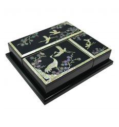 Les accessoires sont présentés sur un plateau en bois laqué noir
